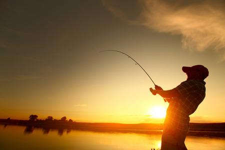 Jonge man vissen vanaf een boot bij zonsondergang