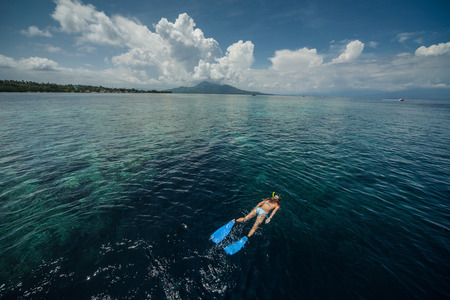 Woman snorkeling in a tropical sea by reefs drop off. Indonesia photo