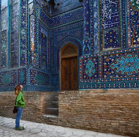 shah: Young lady tourist watching ancient ornament of ancient complex of Shah i Zinda. Samarkand, Uzbekistan Stock Photo