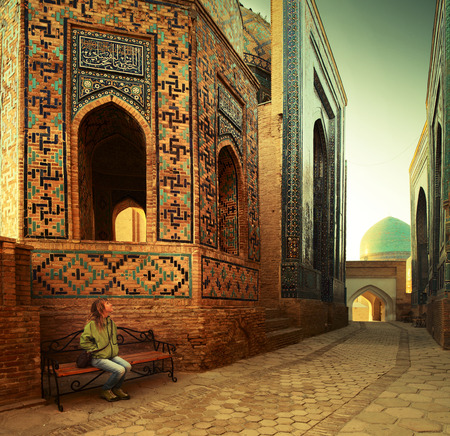 shah: Young lady tourist sitting on a bench and enjoying oriental atmosphere of ancient complex of Shah i Zinda. Samarkand, Uzbekistan