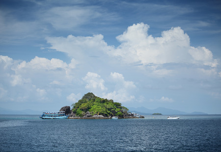 dive trip: Boats around green island in a tropical sea and fluffy clouds. Thailand