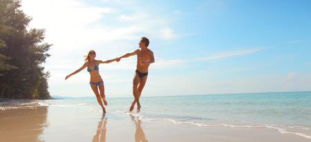 vacaciones en la playa: Pareja feliz corriendo en la playa en un día soleado