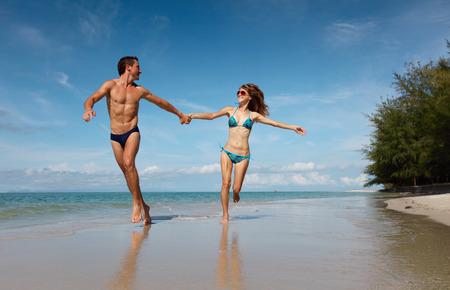 luna de miel: Pareja joven que se divierte en la playa tropical en día soleado Foto de archivo