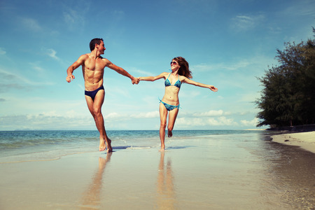 sunny beach: Young couple having fun on the tropical beach at sunny day