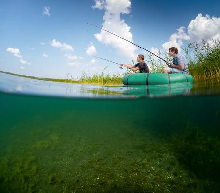 Split shot of two fishermen in the boat in reed Imagens