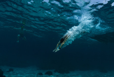 Underwater shot of the man jumping into clear sea water photo