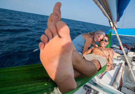 feet relaxing: Young couple relaxing on the yacht in the sea at sunny day