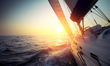Sail boat gliding in open sea at sunset Stock Photo