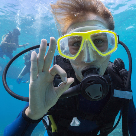Female scuba diver underwater showing ok signal Stock Photo