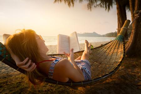 Jonge dame het lezen van een boek in de hangmat op een strand bij zonsondergang