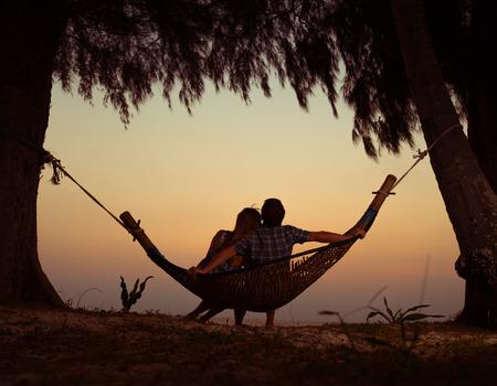 若いカップルの日没でハンモックでリラックス