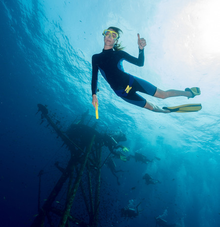bottomless: Free diver on depth with ship wreck on the background