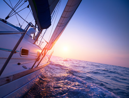Sail boat gliding in open sea at sunset Imagens