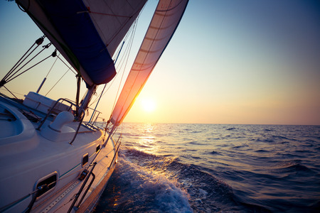 main board: Sail boat gliding in open sea at sunset Stock Photo