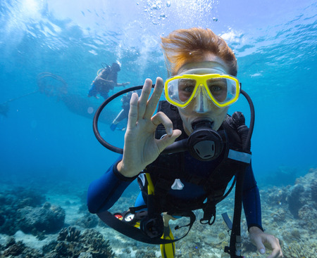 tanks: Female scuba diver underwater showing ok signal Stock Photo