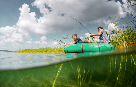 the thicket: Split shot of two fishermen in the boat in reeds thicket and underwater view of the bottom Stock Photo