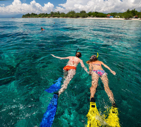 Two ladies snorkeling in tropical sea at sunny day photo