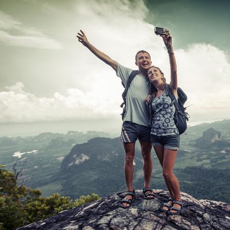 배경에 녹색 계곡과 산 꼭대기에 자신의 사진을 복용 등산객의 커플