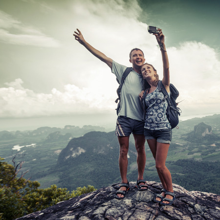 Couple of hikers taking photo of themselves on top of the mountain with green valley on the background Foto de archivo
