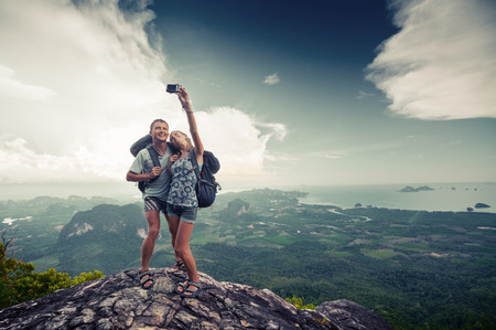 Couple of hikers taking photo of themselves on top of the mountain with green valley on the background photo