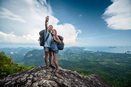 Twee wandelaars nemen selfie op de top van de berg