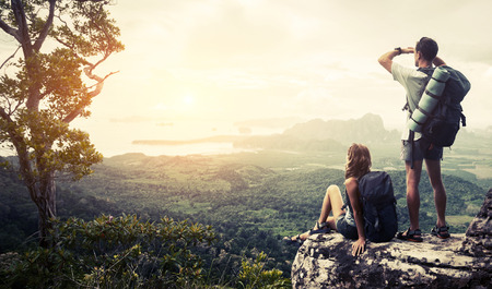 Hikers relaxing on top of the mountain and enjoying green valley view Stock Photo