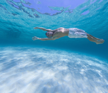 Young man diving on a breath hold in the tropical sea over sandy bottom.