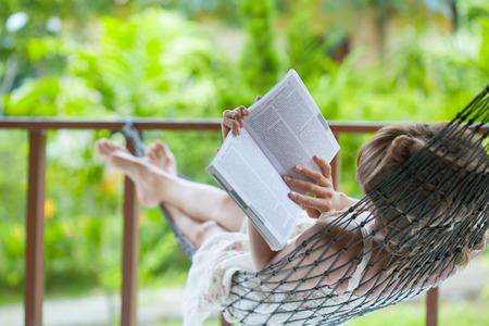 女性、ハンモックで本を読んで