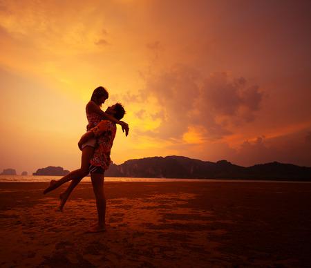 日没で熱帯のビーチでリラックスした若いカップル