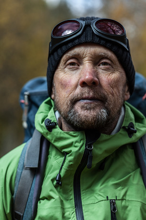 man face close up: Mature backpacker in an autumn forest