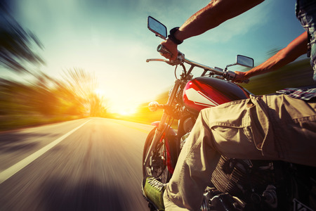 motor bikes: Biker riding motorcycle  on an empty road at sunny day Stock Photo