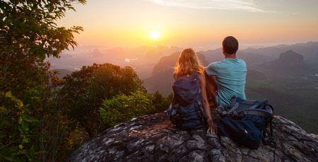 over the hill: Two hikers relaxing on top of hill and enjoying sunrise over the valley Stock Photo
