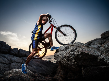 people in action: Bicycle rider crossing rocky terrain at sunset