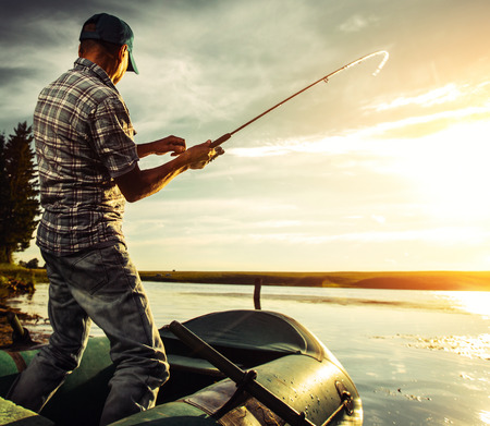 Mature man fishing from the boat at sunset photo