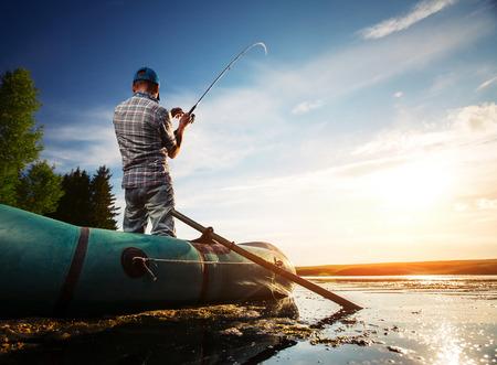 Ältere Menschen Angeln vom Boot auf dem Teich bei Sonnenuntergang Standard-Bild