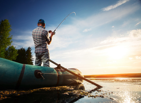 fishing catches: Mature man fishing from the boat on the pond at sunset
