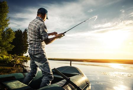 Oudere man vissen vanaf de boot op de vijver bij zonsondergang