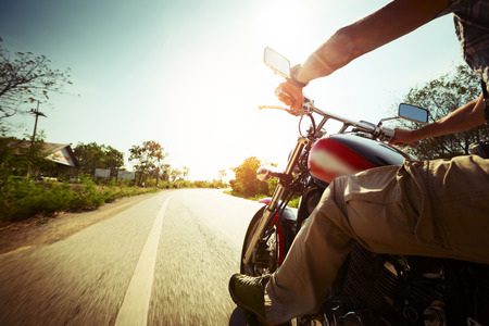 Biker riding motorcycle  on an empty road at sunny day Stock Photo