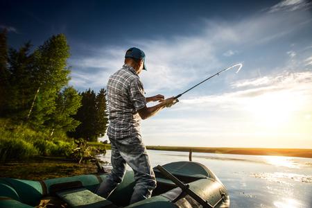 Oudere man vissen vanaf de boot op de vijver bij zonsondergang Stockfoto - 31259814