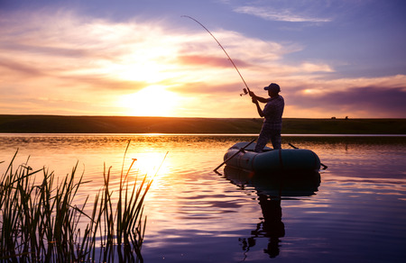 lakes and rivers: Mature man fishing from the boat on the pond at sunset