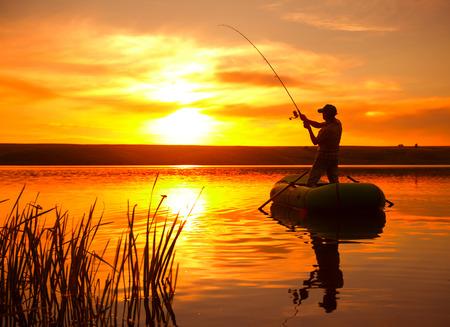 Ältere Menschen Angeln vom Boot auf dem Teich bei Sonnenuntergang