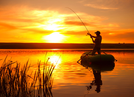 Mature man fishing from the boat on the pond at sunset 免版税图像 - 31259752