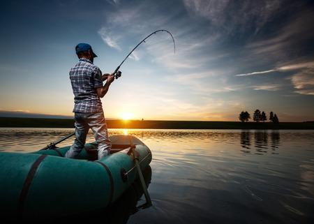hombre pescando: Hombre maduro a pescar desde el barco en el estanque al atardecer