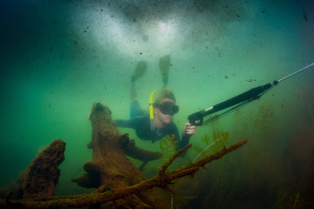 speargun: Underwater shot of the hunter diving with speargun in the lake with poor visibility