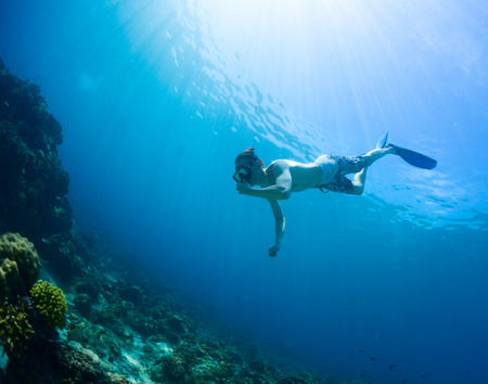 free diving: Underwater shot of the man moving towards the coral reef Stock Photo