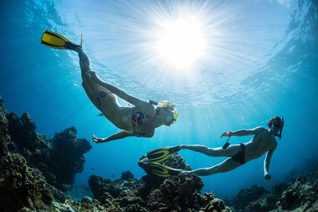 Onderwater schot van de paar bewegen op diepte over koraalrif