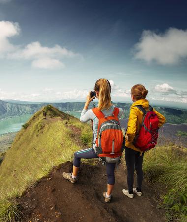 amateur: Los excursionistas de pie en la cima de la montaña y que toman el cuadro del valle Foto de archivo