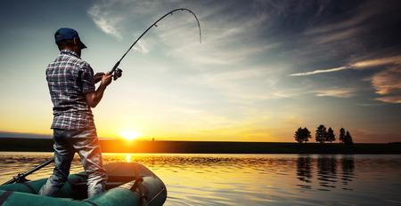 hengelsport: Oudere man vissen vanaf de boot op de vijver bij zonsondergang