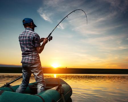 bateau: Homme d'âge mûr de pêche du bateau sur l'étang au coucher du soleil