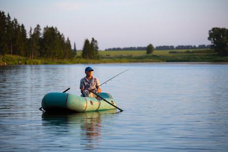 일몰 연못에 보트에서 낚시 성숙한 남자